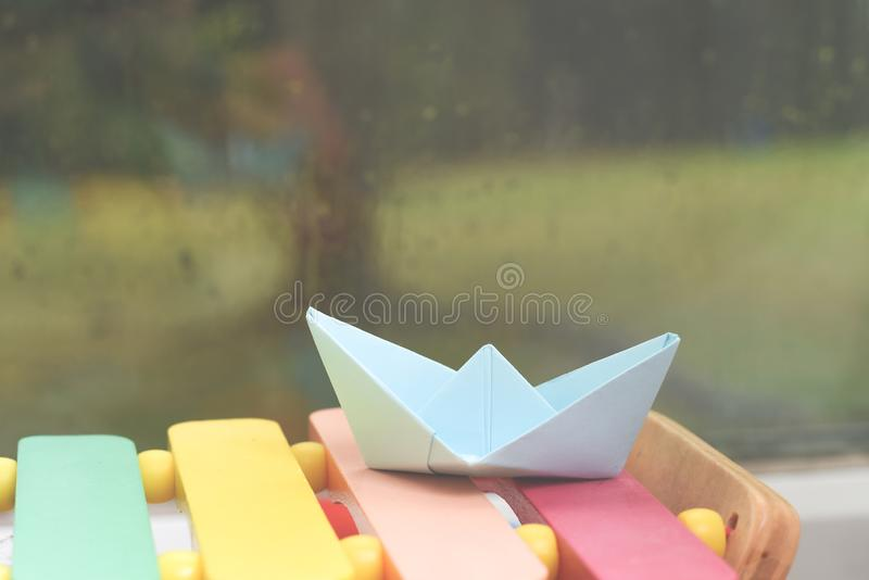 Origami boat by a window on a rainy day inside the house. Origami hand made boat by a window on a rainy day inside the house stock images