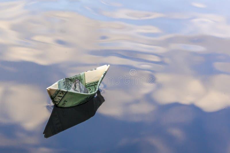 Origami-boot gebouwd op honderd dollar rekening papieren boot van honderd dollar biljet in blauw water kopieerruimte Begrip: stock afbeeldingen