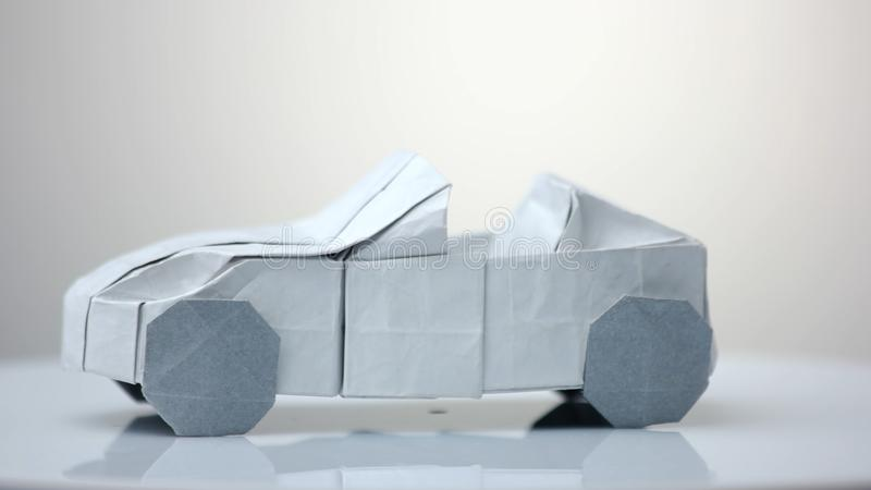 Origami car model on white background. Exhibition of paper decorations stock photo