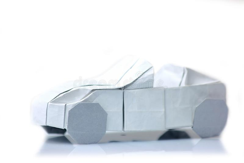 Origami car model on white. Vehicle figurine made of folded paper. Art exposition item royalty free stock photo