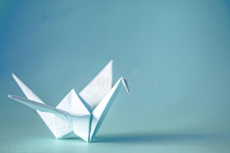 Origami crane from paper on a plain background,copy space stock photography