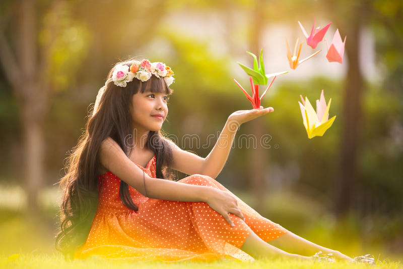 Origami cranes. Little cute girl sitting on grass in park with origami cranes, Outdoor portrait royalty free stock image