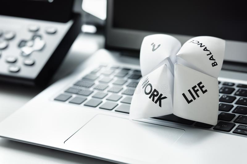 Work life balance choices. Origami fortune teller on laptop in office concept for work life balance choices stock photography