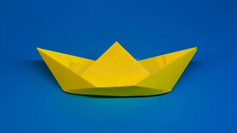 Origami gult skepp av papper på blå bakgrund, hobby arkivfoton
