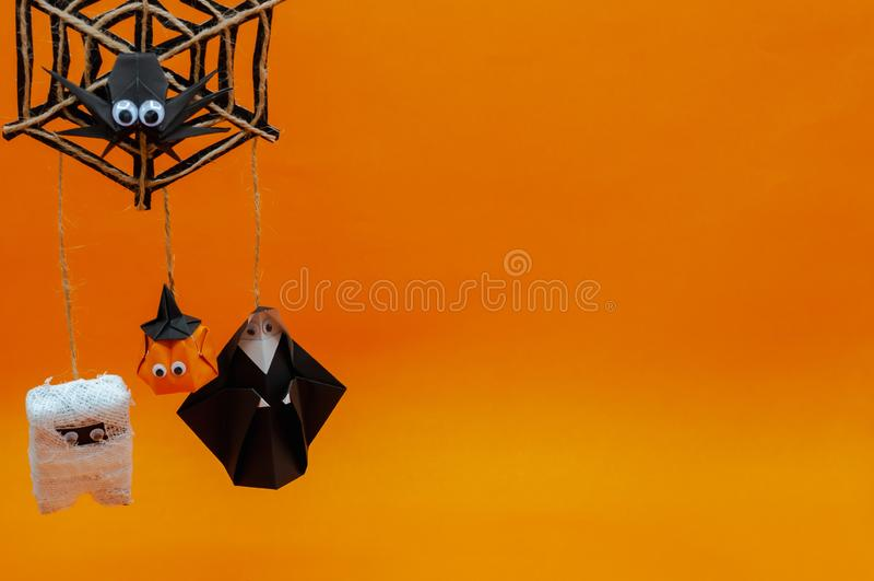Origami Halloweenowy tło bani głowy lampion, mamusia i magdalenki obwieszenie na pająk pajęczynie na pomarańczowym tle, fotografia stock