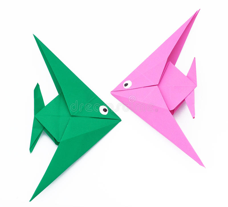 Origami paper fish. Two little origami angel fishes on white background, isolated. Pink and green royalty free stock image