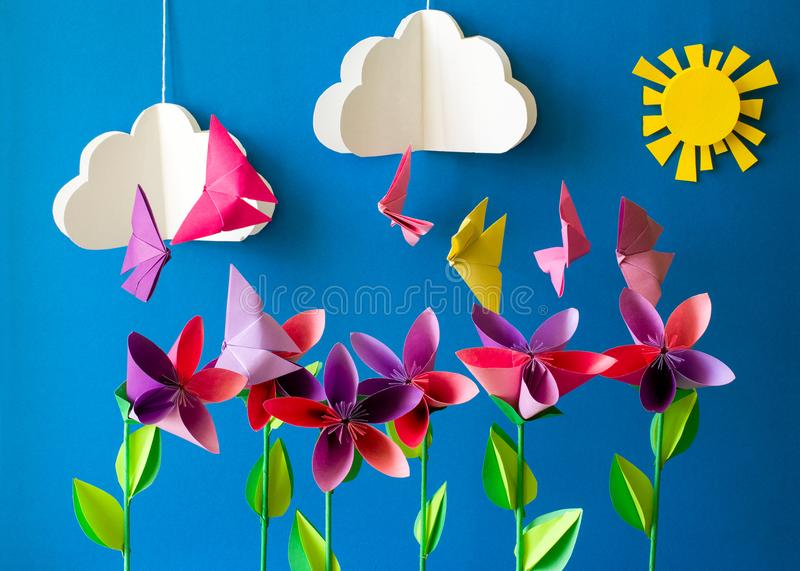 Origami paper flowers, butterflies, clouds and sun. stock photos