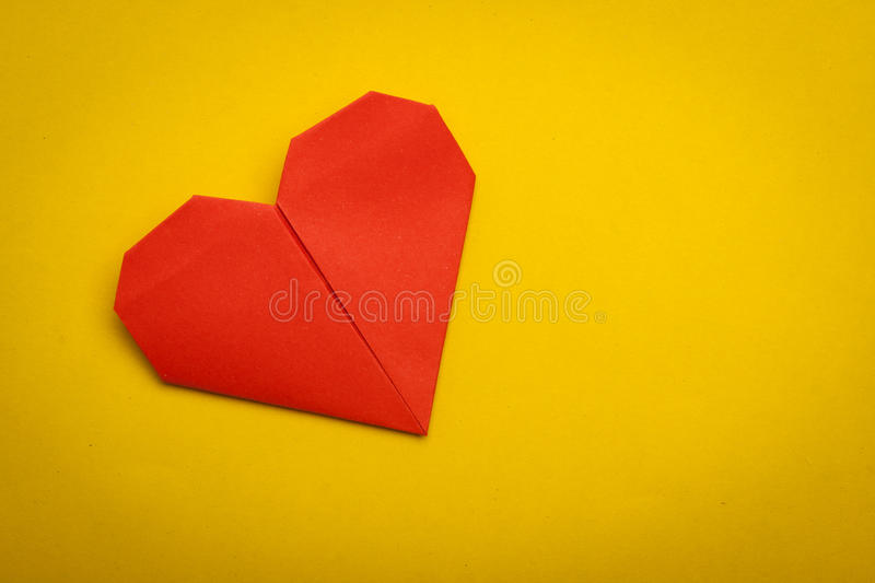 Origami paper heart. Red origami paper heart on yellow paper background royalty free stock images