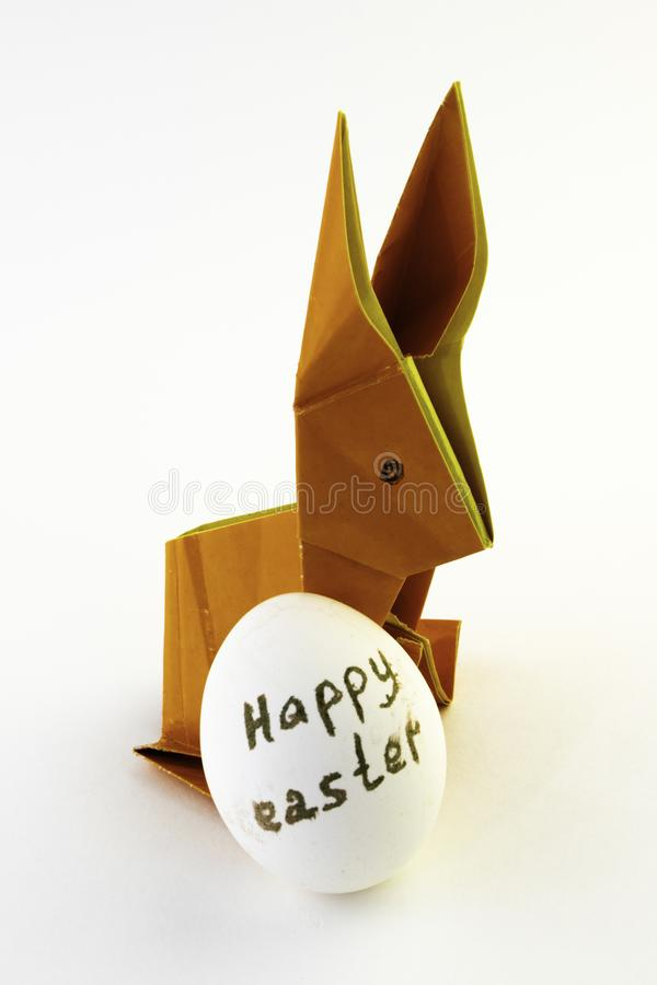 Origami rabbit from orange colored paper. Easter bunny and white chicken egg with the inscription Happy Easter on a white stock photos