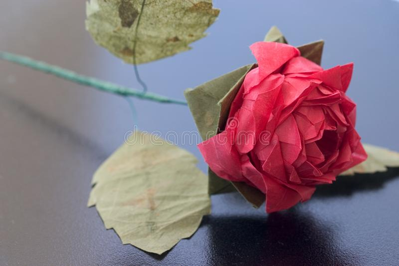 Origami rose on black table stock images