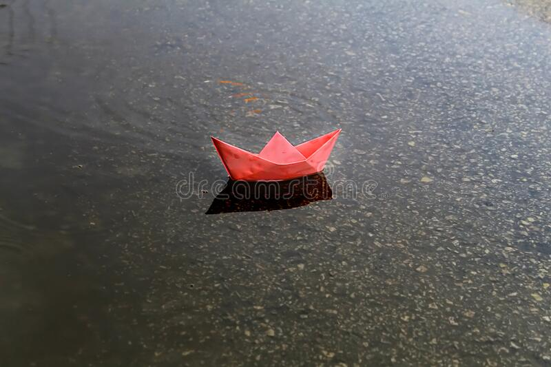 Origami Ship or Paper Boat sails in a puddle formed after rain. Rainy weather, winter in Israel stock image