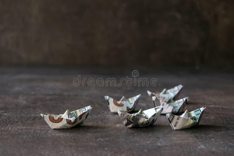 Origami statki od USA dolarów na ciemnym tle Wiele łódź zdjęcie royalty free