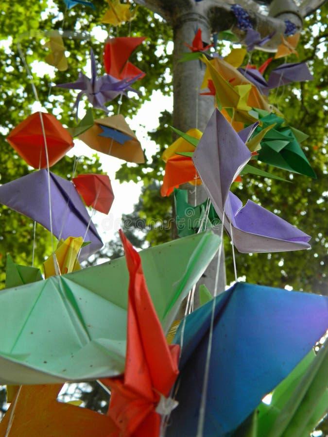 Origami variopinti che appendono nel parco della città fotografia stock libera da diritti
