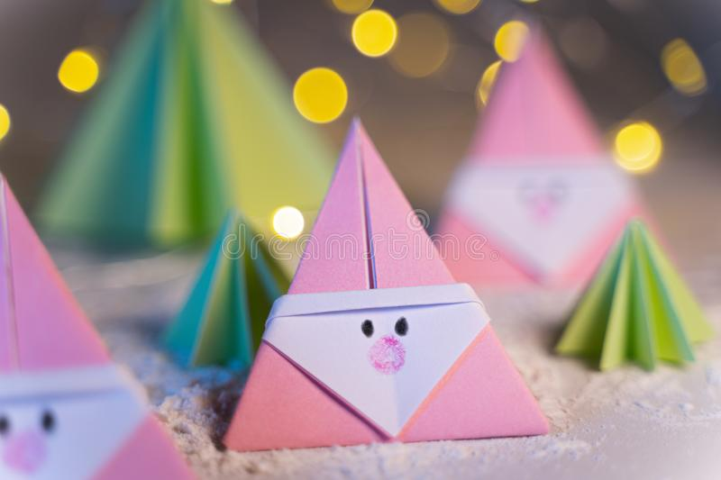Origami Xmas scene with Santa claus and crhistmas trees in paper craft stock images