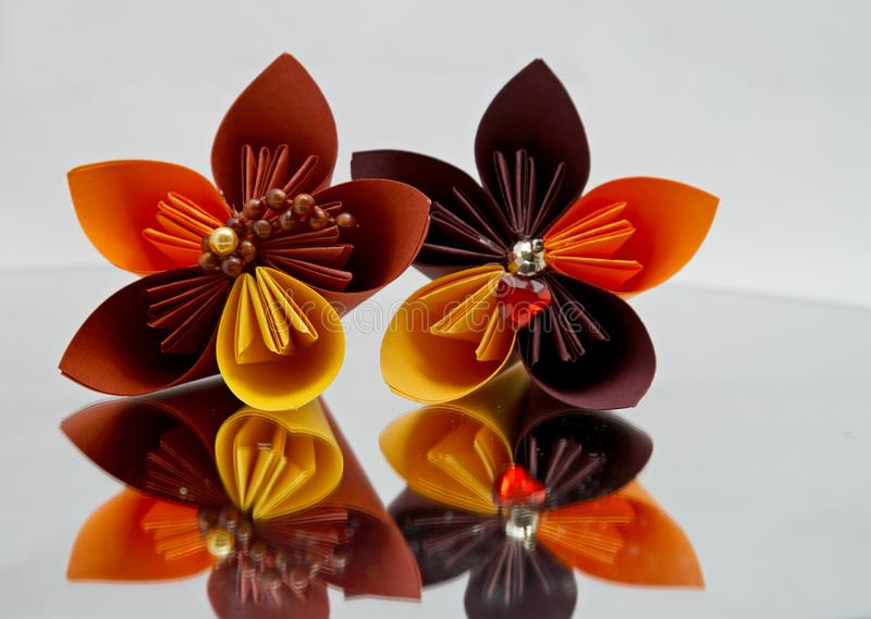 Origamiblommor på en spegel arkivfoto