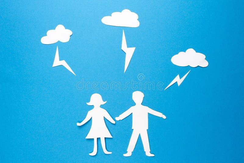 Origamidocument de man en de vrouw houden handen onder bliksemstakingen Brandkast en verzekeringsfamilie ongevallenbescherming royalty-vrije stock foto