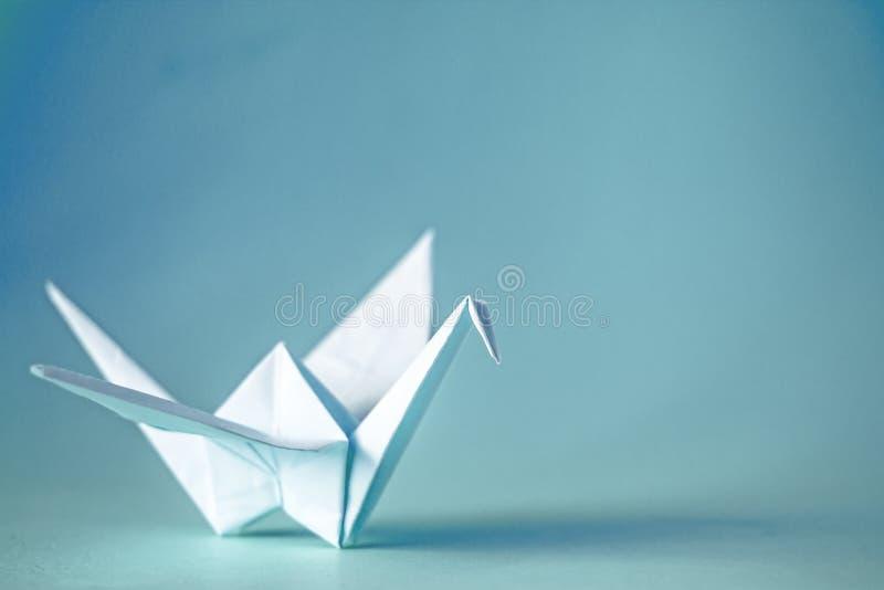 Origamikraan van document op een duidelijke achtergrond, exemplaarruimte stock fotografie