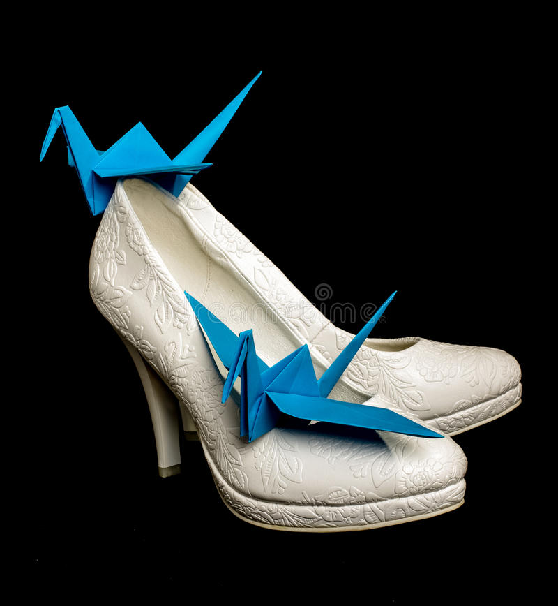 Origamipapperskranar på de brud- skorna fotografering för bildbyråer