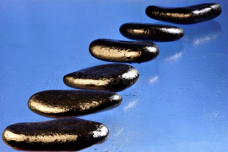 Origen natural mojado negro de las piedras en un fondo azul alineado en fila foto de archivo