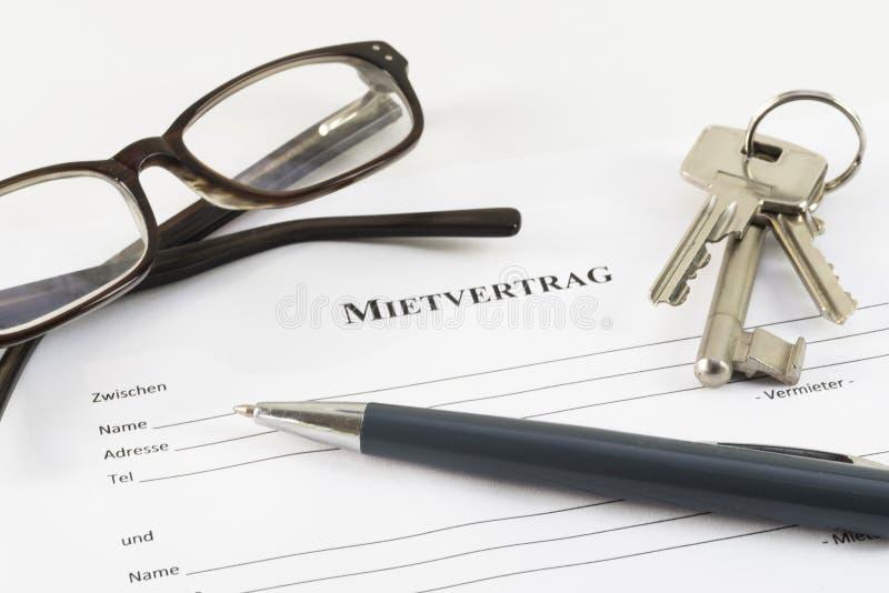 Original alemão do acordo de aluguer com chaves, vidros e a da casa fotografia de stock