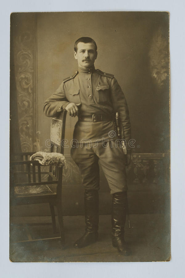 Original 1917 antique photo of an Imperial Russian military officer. Standing in the studio leaning on a chair with a sword stock photos