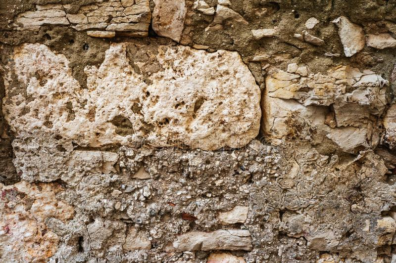 Original background of natural ancient large stone on the wall with the texture of cracks and bricks royalty free stock images