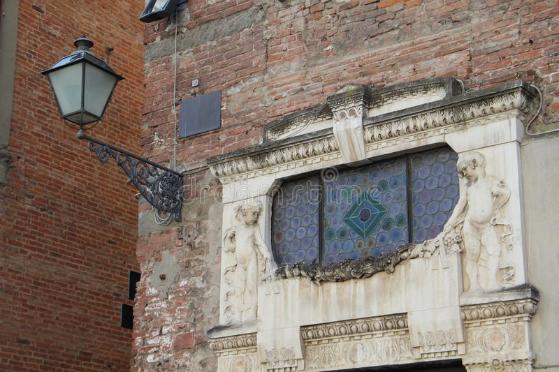 The original bas-relief and lantern of the National Bank of Livorno in the city of Lucca, Italy. The picture was taken on August 6, 2015 stock photography