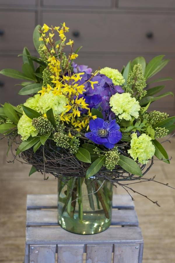 The original bouquet of blue anemones, carnations, forsythia stands in a glass vase royalty free stock images