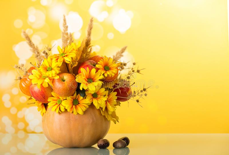 Original bouquet from flowers and fruits in pumpkin vase, next to chestnuts on yellow background stock images