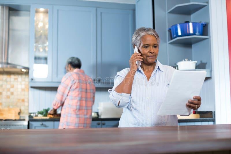 Original da leitura da mulher ao estar na cozinha imagens de stock royalty free