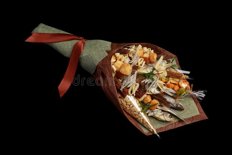 Original- dekorerad gåva för ett ölparti i form av en bukett av den torkade rimmade fisken, jordnötter, smällaren och andra mella fotografering för bildbyråer