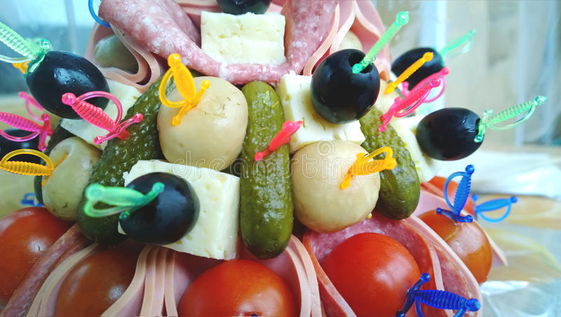 The original design of the appetizers on the table - pickles and olives, salami, tomatoes and cheese. On skewers royalty free stock photo