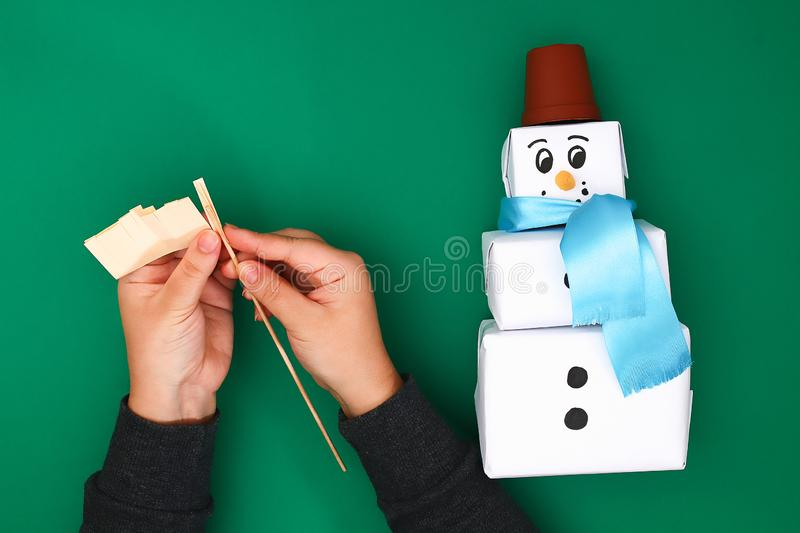 The original design of the three Christmas gift of white paper, a satin ribbon in the form of a snowman on a green background. stock photos