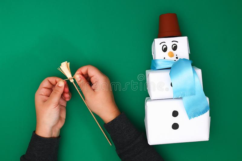 The original design of the three Christmas gift of white paper, a satin ribbon in the form of a snowman on a green background. royalty free stock images