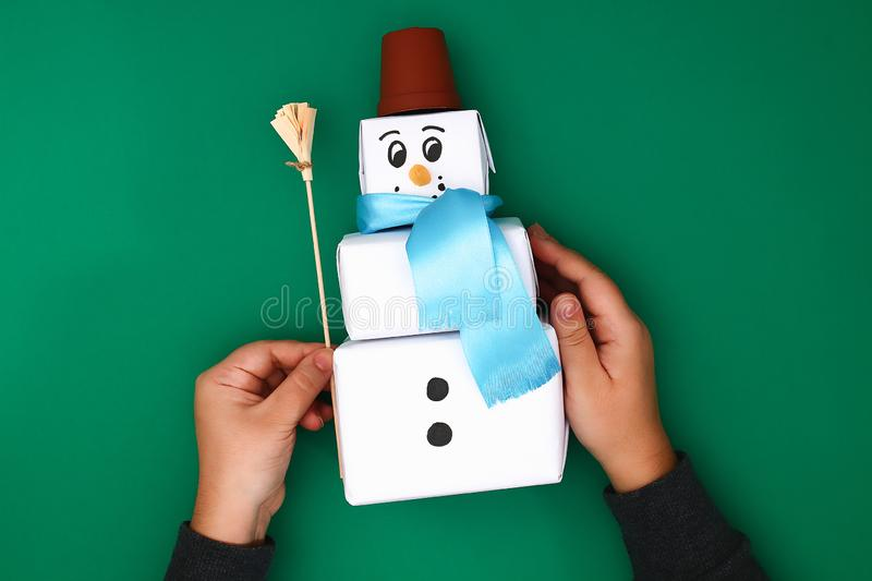 The original design of the three Christmas gift of white paper, a satin ribbon in the form of a snowman on a green background. stock photography