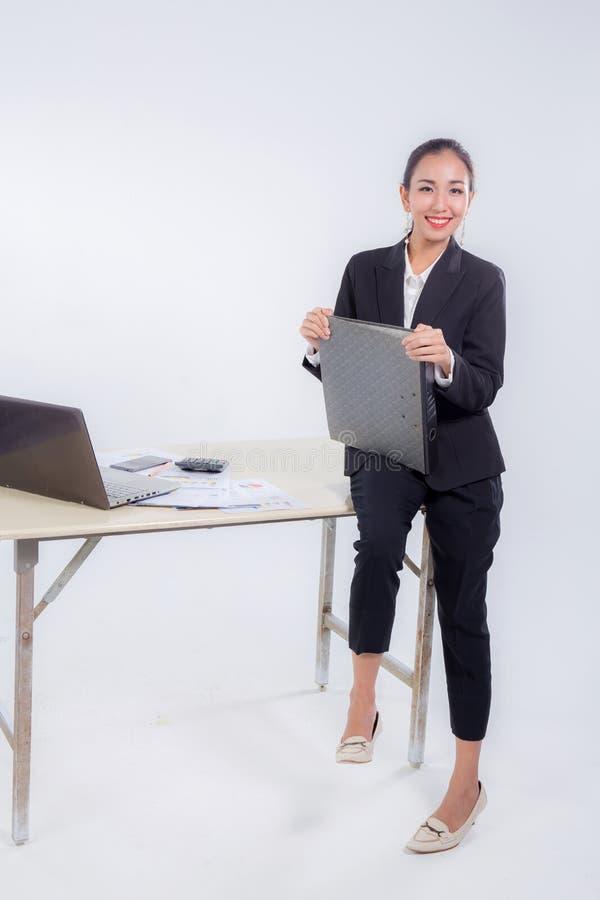 Original do arquivo de posse da mulher de negócios que olha a câmera com a tabela de assento no escritório fotos de stock royalty free