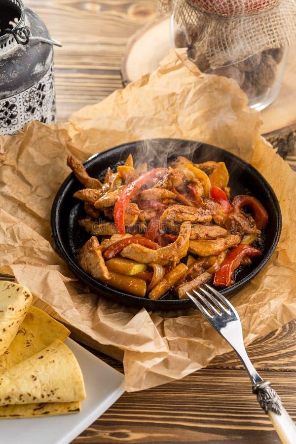 Original fajita sizzling smoking hot served on iron plate on wooden table stock photos