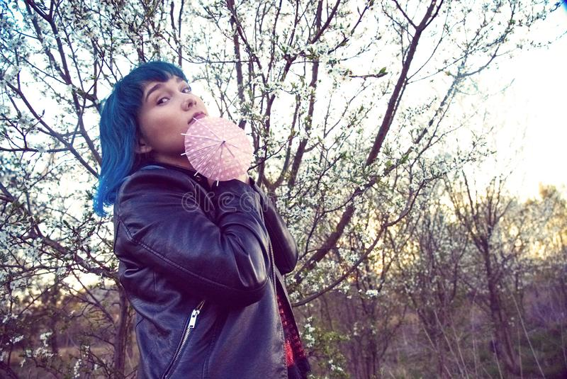 The original fashion photo of a young girl in blue hair. The original fashion photo of a young girl with dark hair and a small pink umbrella stock photos