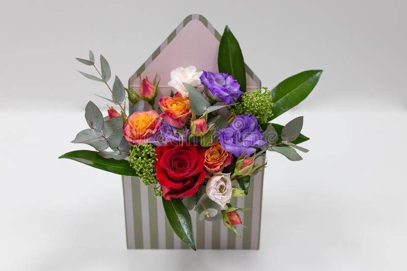 Original floral arrangement gift of fresh flowers in a box in the form of an envelope on a light background. Flowers: roses, eustoma, leaves. Primary colors royalty free stock images