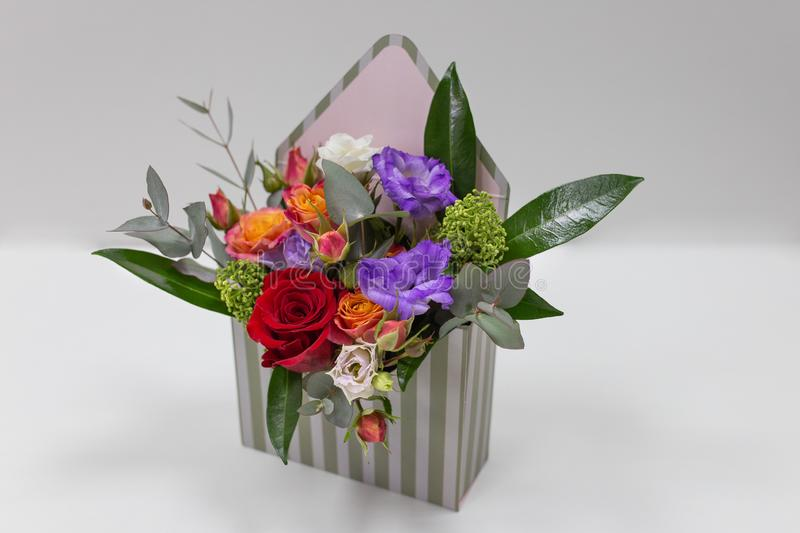 Original floral arrangement gift of fresh flowers in a box in the form of an envelope on a light background. Flowers: roses, eustoma, leaves. Primary colors stock photos