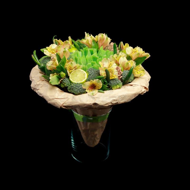 Original- gåva i form av en bukett av blommor, grönsaker och grön ost som står i en exponeringsglasvas som isoleras på en svart b arkivfoton