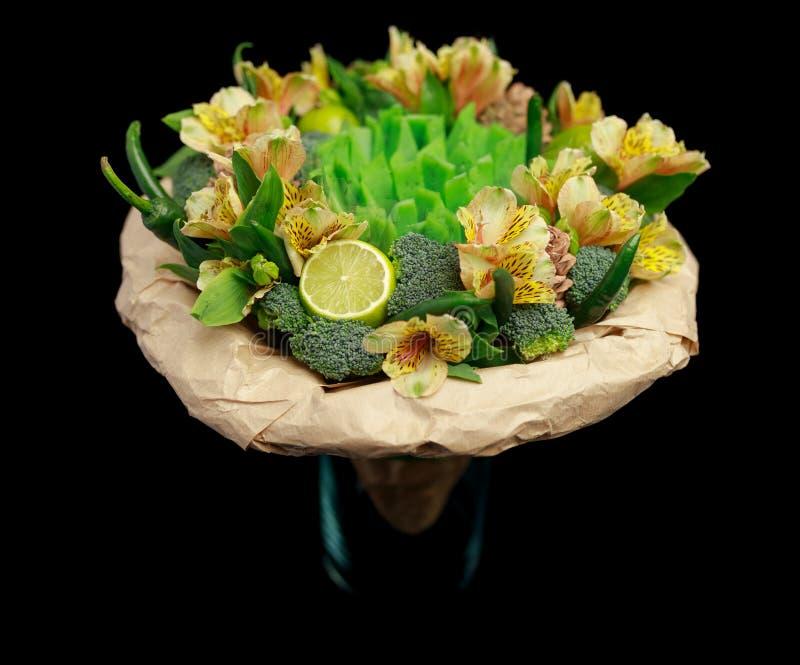 Original- gåva i form av en bukett av blommor, grönsaker och grön ost som står i en exponeringsglasvas som isoleras på en svart b royaltyfria bilder