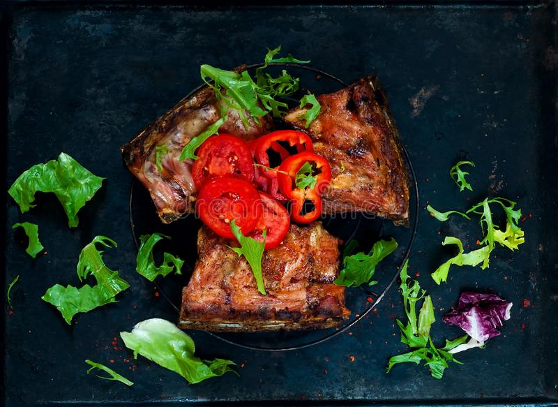 The Original Grilled Ribs with tomatoes and arugula salad on cutting board on dark background.The finest ribs with spices. royalty free stock image