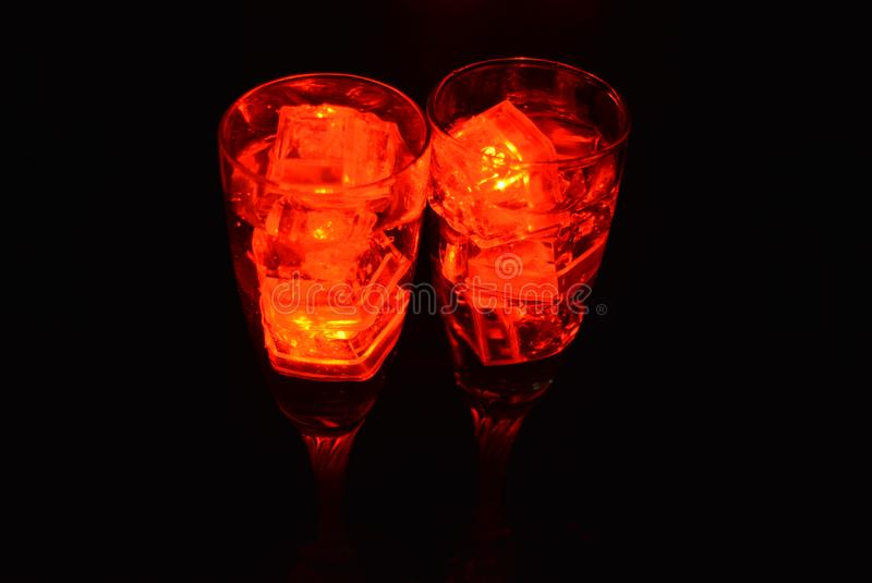 Two unusual glasses of champagne with a drink and bright red ice chips. Original image of love and mysticism in the form of two glasses of champagne with a red stock photos