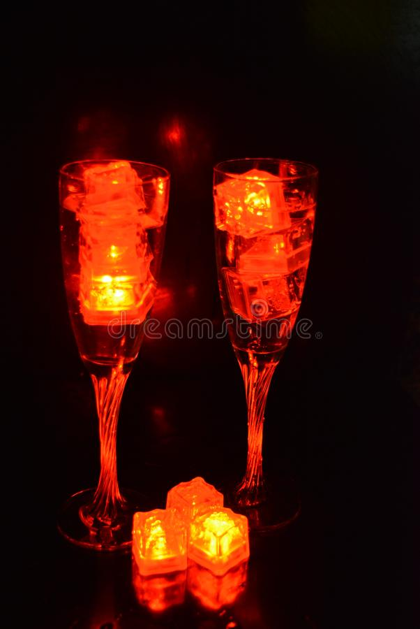 Two unusual glasses of champagne with a drink and bright red ice chips. Original image of love and mysticism in the form of two glasses of champagne with a red stock photography