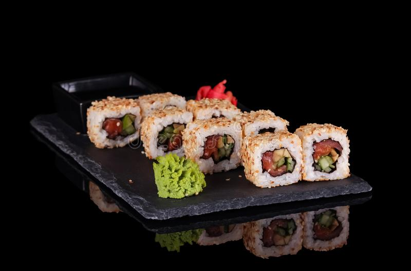 Original Japanese dish rolls with seafood, ginger and wasabi isolated on black stock image