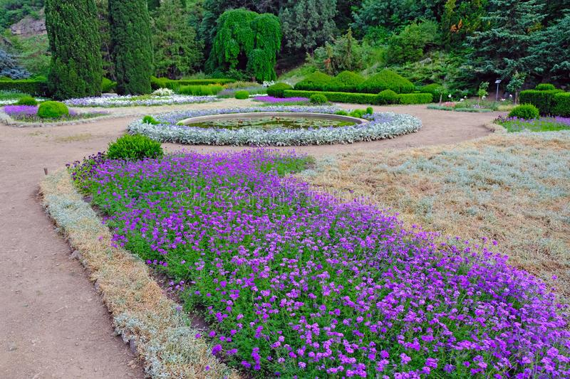 Original landscape design in the botanical garden in Tbilisi. Beautiful park with flower beds, exactly cut trees and a small pond in the summer stock image
