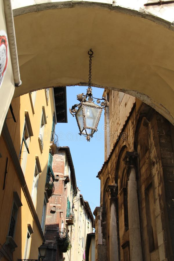 The original lantern on the chain in the archway of the house in Lucca, Italy. The picture was taken on August 6, 2015 royalty free stock image