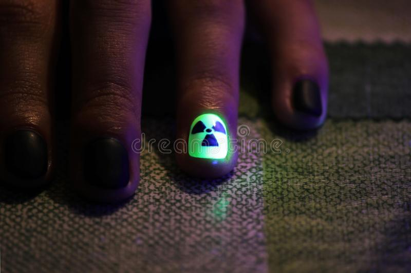 The original manicure in the form of a radioactive danger sign with gel shellac varnish, glows in the dark with. Ultraviolet light royalty free stock image