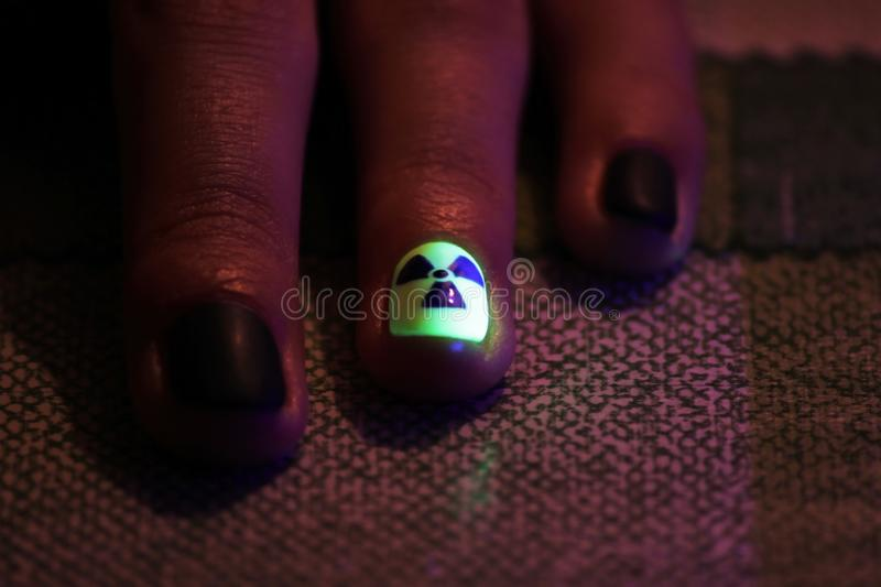 The original manicure in the form of a radioactive danger sign with gel shellac varnish, glows in the dark with. Ultraviolet light stock images